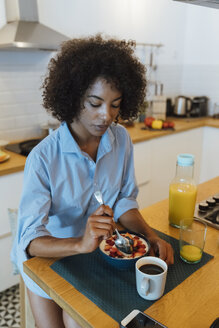 Woman having breakfast in her kitchen, eating fruit - BOYF01010