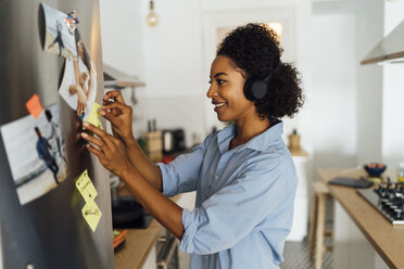 Woman in her kitchen in the morning, posting sticky  notes on the fridge - BOYF01022
