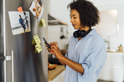 Woman in her kitchen in the morning, posting sticky  notes on the fridge - BOYF01025