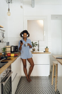 Woman with headphones, using smartphone and drinking coffee for breakfast in her kitchen - BOYF01031