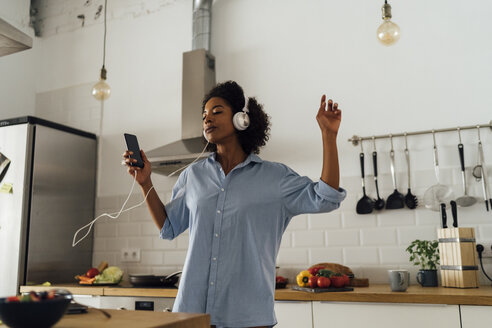 Woman dancing and listening music in the morning in her kitchen - BOYF01043