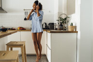 Woman dancing and listening music in the morning in her kitchen - BOYF01046