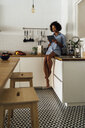 Woman sitting on worktop of her kitchen, using digital tablet in the morning - BOYF01052