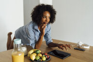 Woman using digital tablet and having a healthy breakfast in her kitchen - BOYF01058