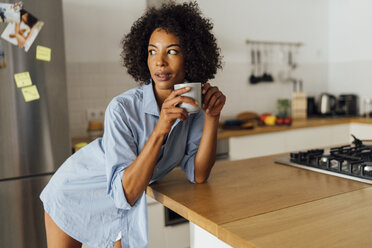 Woman standng in her kitchen, having her morning coffee - BOYF01067