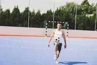 Full length of young man practicing soccer on court during sunny day - CAVF54564