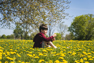 Side view of boy with broken leg sitting amidst yellow flowering plants on field at park during sunny day - CAVF54600
