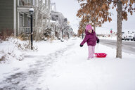 Cute girl pulling sled while walking on snow covered road - CAVF54636