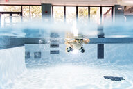 Shirtless boy swimming in pool - CAVF54660