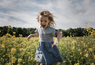 Happy girl running standing amidst plants against cloudy sky - CAVF54675