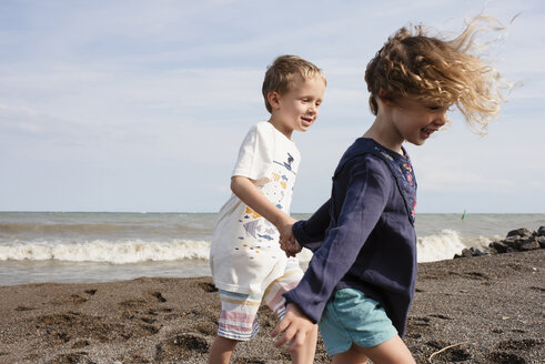 Happy siblings holding hands while walking at beach against sky during sunny day - CAVF54681