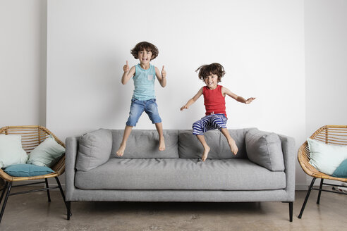 Portrait of happy brothers jumping on sofa against wall at home - CAVF54684