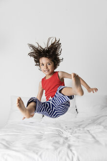 Portrait of happy boy jumping on bed against wall at home - CAVF54693