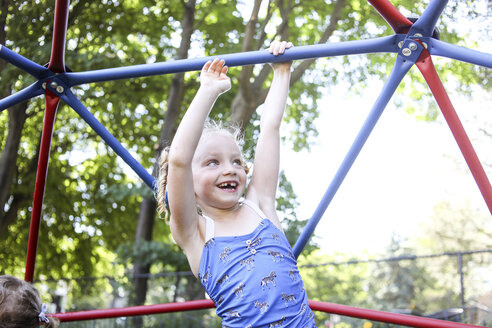 Happy cute girl climbing jungle gym against trees at playground - CAVF54702