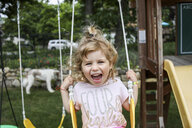 Portrait of happy girl screaming while swinging at playground - CAVF54705