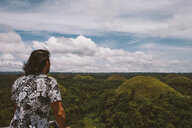 Rear view of man looking at Chocolate Hills while standing by railing against cloudy sky - CAVF54753
