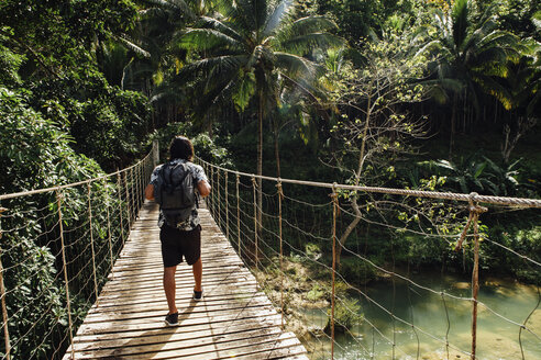 Rear view of man with backpack walking on footbridge over river in forest - CAVF54756