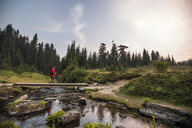 Side view of hiker crossing stream on overpass - CAVF54774