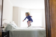 Side view of happy girl jumping on bed at home - CAVF54777