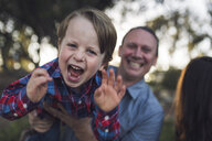 Portrait of playful son carried by father at park - CAVF54786