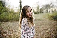 Portrait of confident girl standing at park - CAVF54798