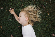 High angle view of cheerful girl lying on grassy field at park - CAVF54819