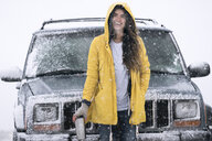 Portrait of cheerful woman standing by off-road vehicle on field during winter - CAVF54828