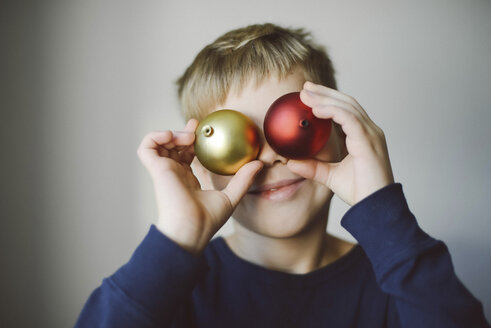 Playful boy holding baubles against face at home - CAVF54864