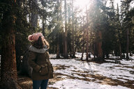 Woman wearing warm clothing while standing at forest during winter - CAVF54870