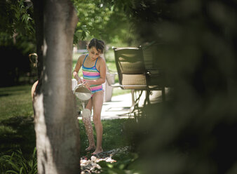 Girl wearing swimwear while watering plants at yard - CAVF54903