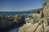 Side view of woman sitting on rocks at beach against clear sky - CAVF54927