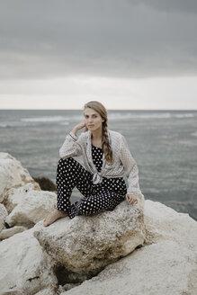 Full length portrait of woman sitting on rocks at beach against cloudy sky - CAVF54939