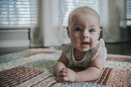Portrait of cute baby girl lying on bed at home - CAVF54945