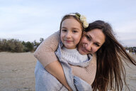 Portrait of smiling mother embracing daughter while standing at beach against sky - CAVF54957