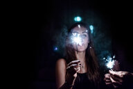 A young woman holding illuminated sparklers at night - INGF07687