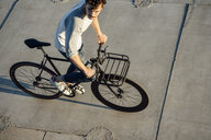 Young man riding commuter fixie bike on concrete slabs - VPIF01034