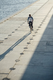 Young man riding bike on waterfront promenade at the riverside - VPIF01037