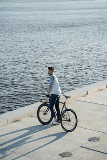 Young man with commuter fixie bike having a break at the riverside - VPIF01040