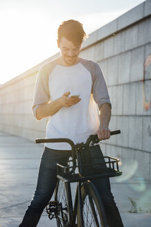 Smiling young man with commuter fixie bike looking at cell phone - VPIF01043