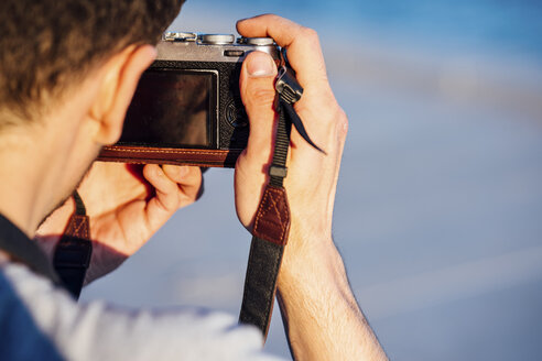 Close-up of young man taking picture with old-fashioned camera - VPIF01052