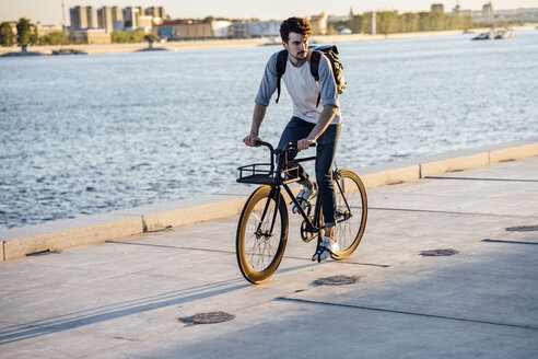 Young man with backpack riding bike on waterfront promenade at the riverside - VPIF01055