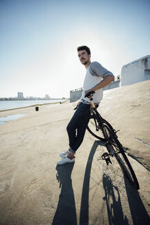 Young man with commuter fixie bike having a break at concrete wall - VPIF01079