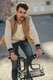 Portrait of young man riding commuter fixie bike in the city - VPIF01094