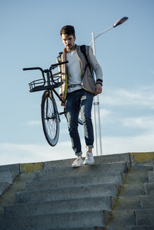 Young man carrying commuter fixie bike walking down stairs - VPIF01100