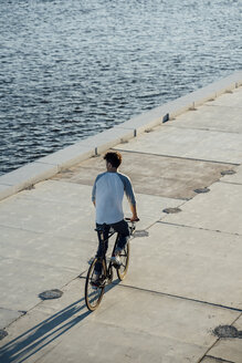 Young man riding bike on waterfront promenade at the riverside - VPIF01103
