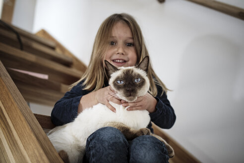 Little girl sitting on stairs with her Siamese cat at home - KMKF00639