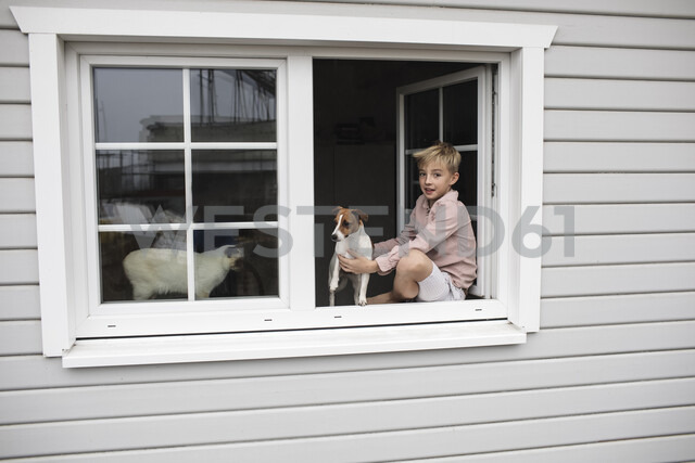Portrait of boy sitting on window sill with Jack Russel Terrier and Siam cat looking out of open window - KMKF00645