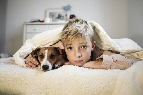 Portrait of blond boy and his Jack Russel Terrier lying together on bed - KMKF00648