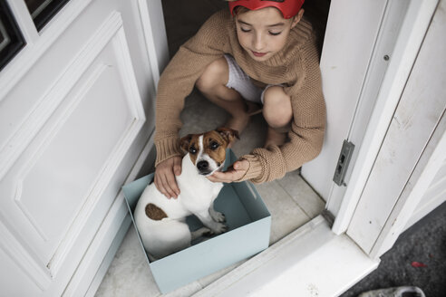 Boy with Jack Russel Terrier sitting in a cardboard box at house entrance - KMKF00657