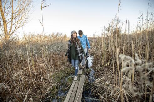 Couple hiking together through tall grass, Portland, Maine, USA - AURF07799